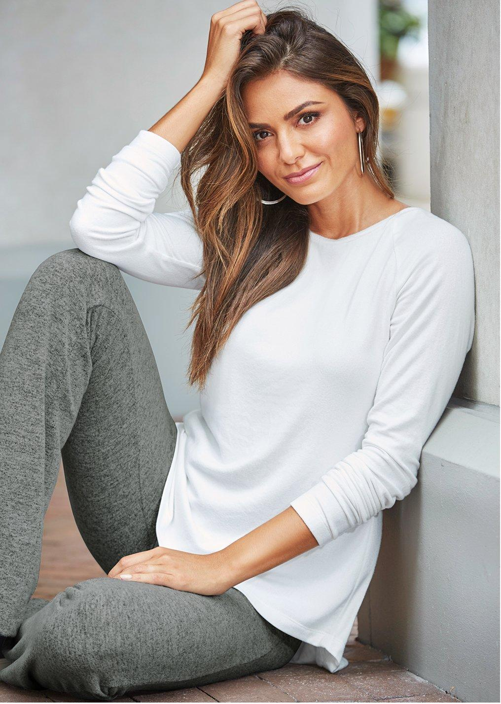 model wearing a white sweater over gray yoga pants