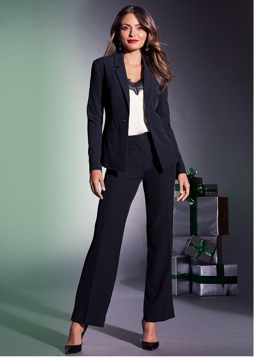 model wearing a black blazer with black pants over a white tank top with black lace