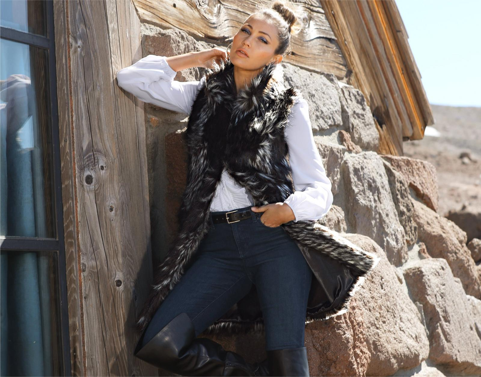model wearing faux fur vest over white ruffle blouse and jeans with black over-the-knee boots