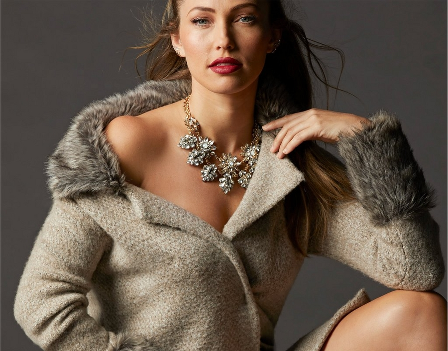 model wearing tan faux fur sweater coat with a large statement necklace