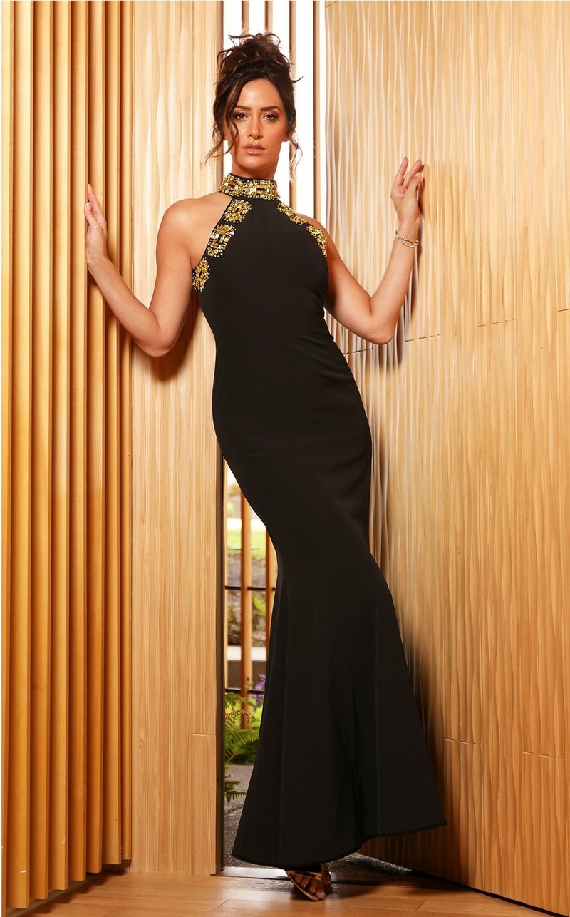 model wearing black high neck gown with gold embellishments lining the neck and sides