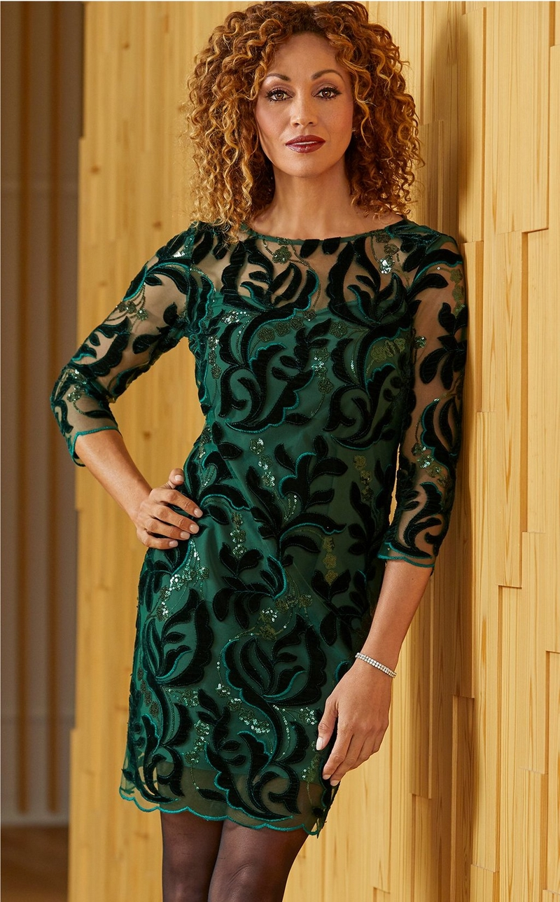 Model wearing a knee length green embellished illusion dress with long sleeves