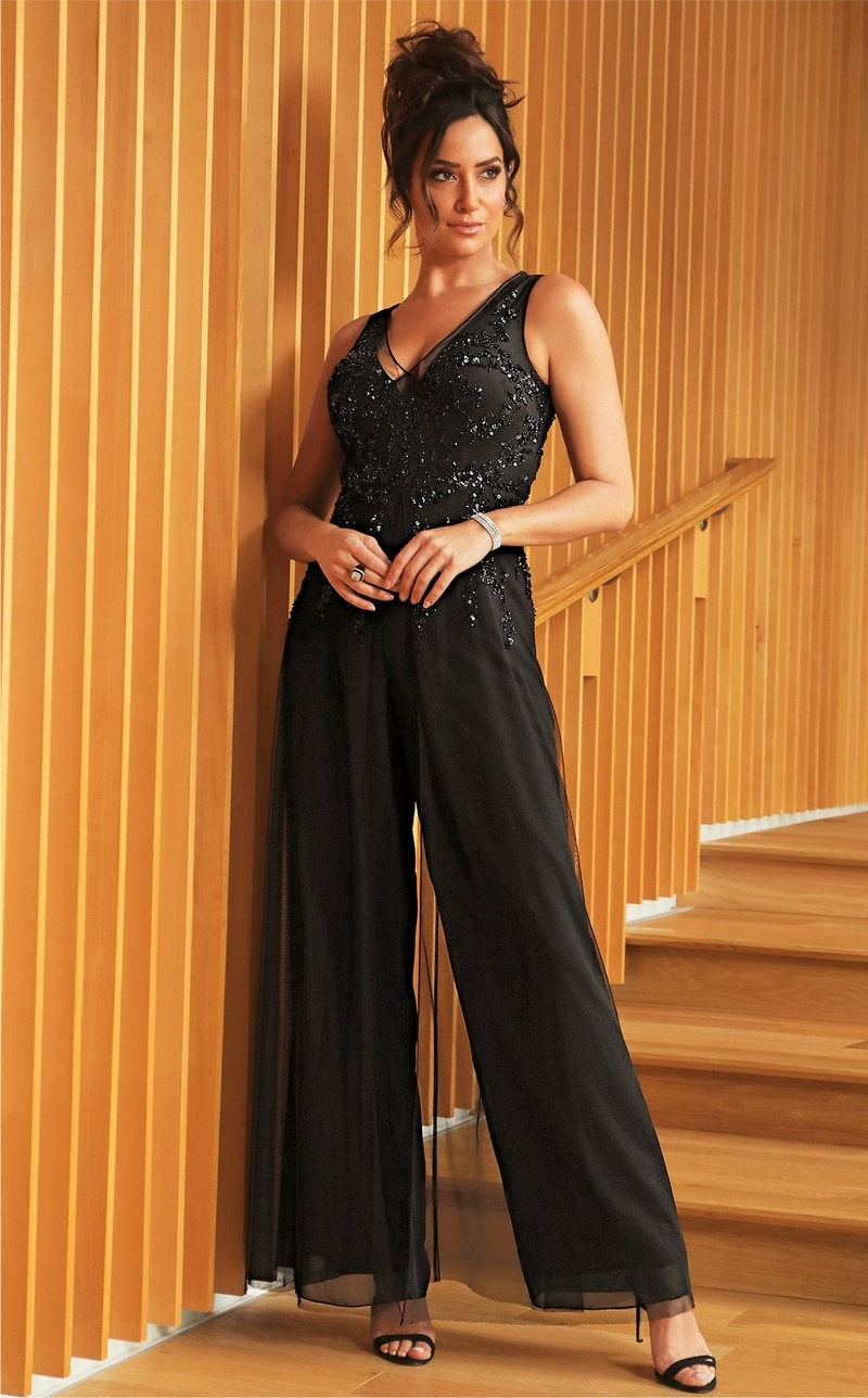 model wearing black and sleeveless beaded jumpsuit