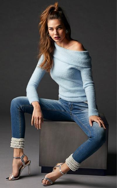 model wearing sky blue, off the shoulder sweater over pearl embellished jeans