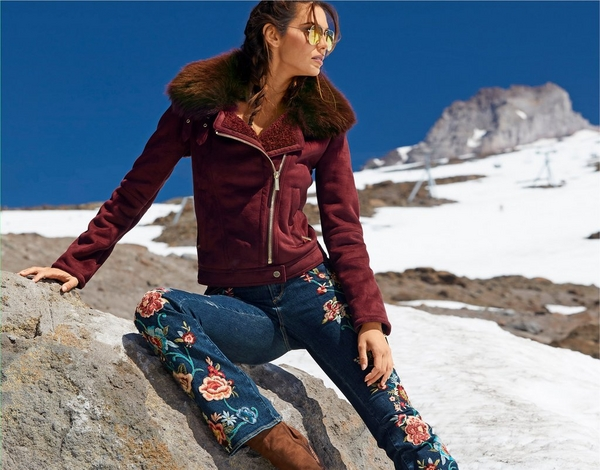 model wearing wine colored faux fur jacket with flower embellished jeans