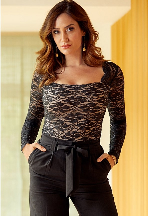 model wearing black and nude lace top with black tie waist crepe pants