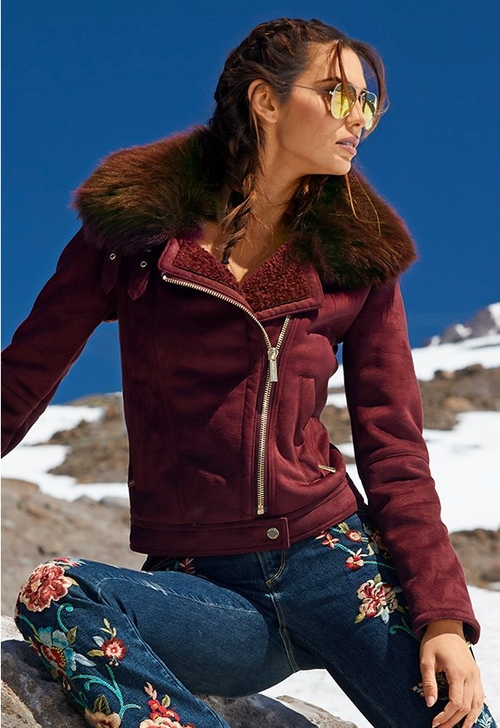 model wearing maroon zip up jacket with fur lined collar over floral embroidered jeans