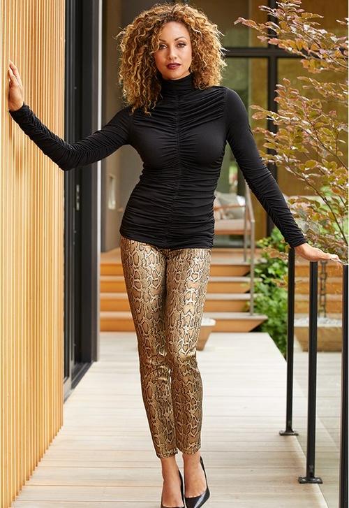 model wearing gold snake print pants and ruched black turtleneck top