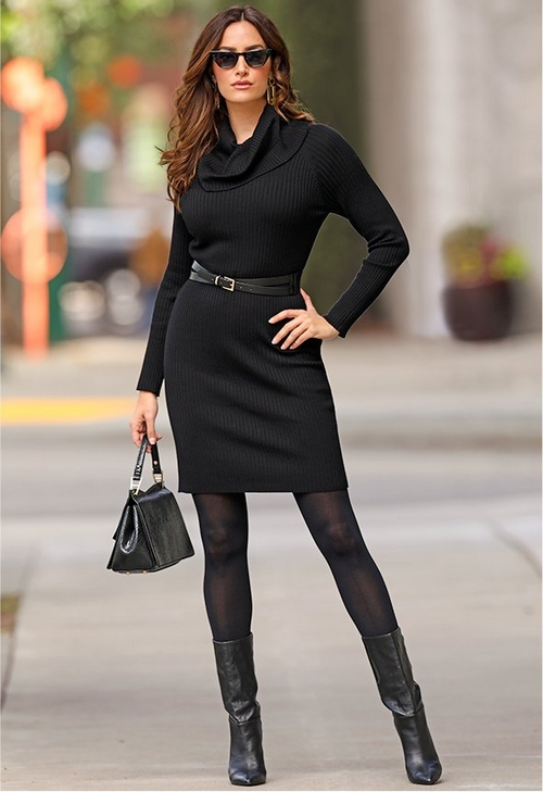 model wearing black cowl neck sweater dress over tights with boots and a black handbag