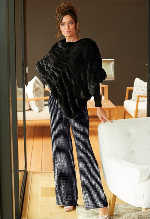model wearing faux fur poncho over sparkly black palazzo pants
