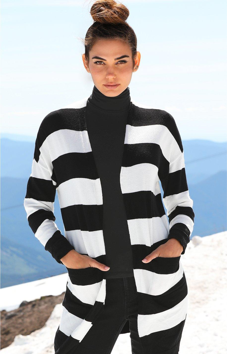 model wearing a black and white striped cardigan over a black turtleneck