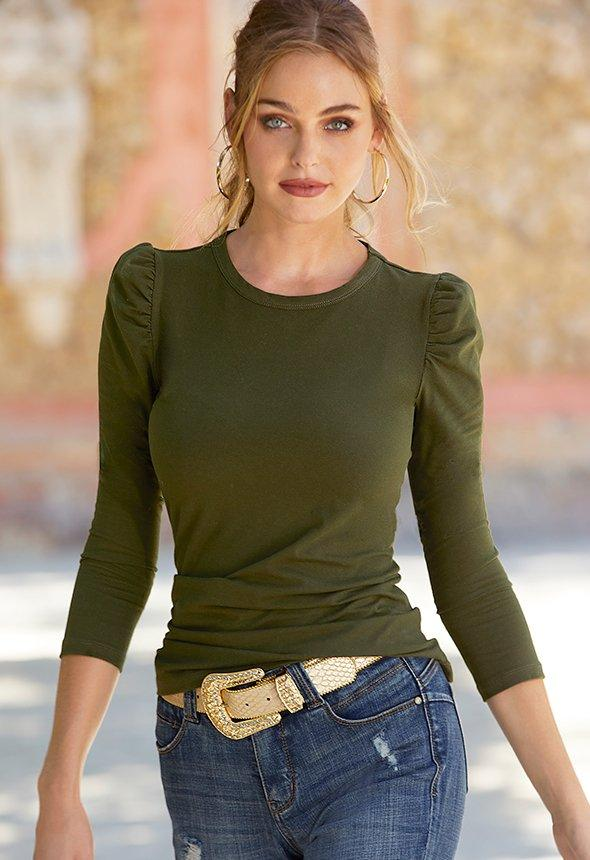 model wearing olive puff sleeve top with gold belt and ripped jeans