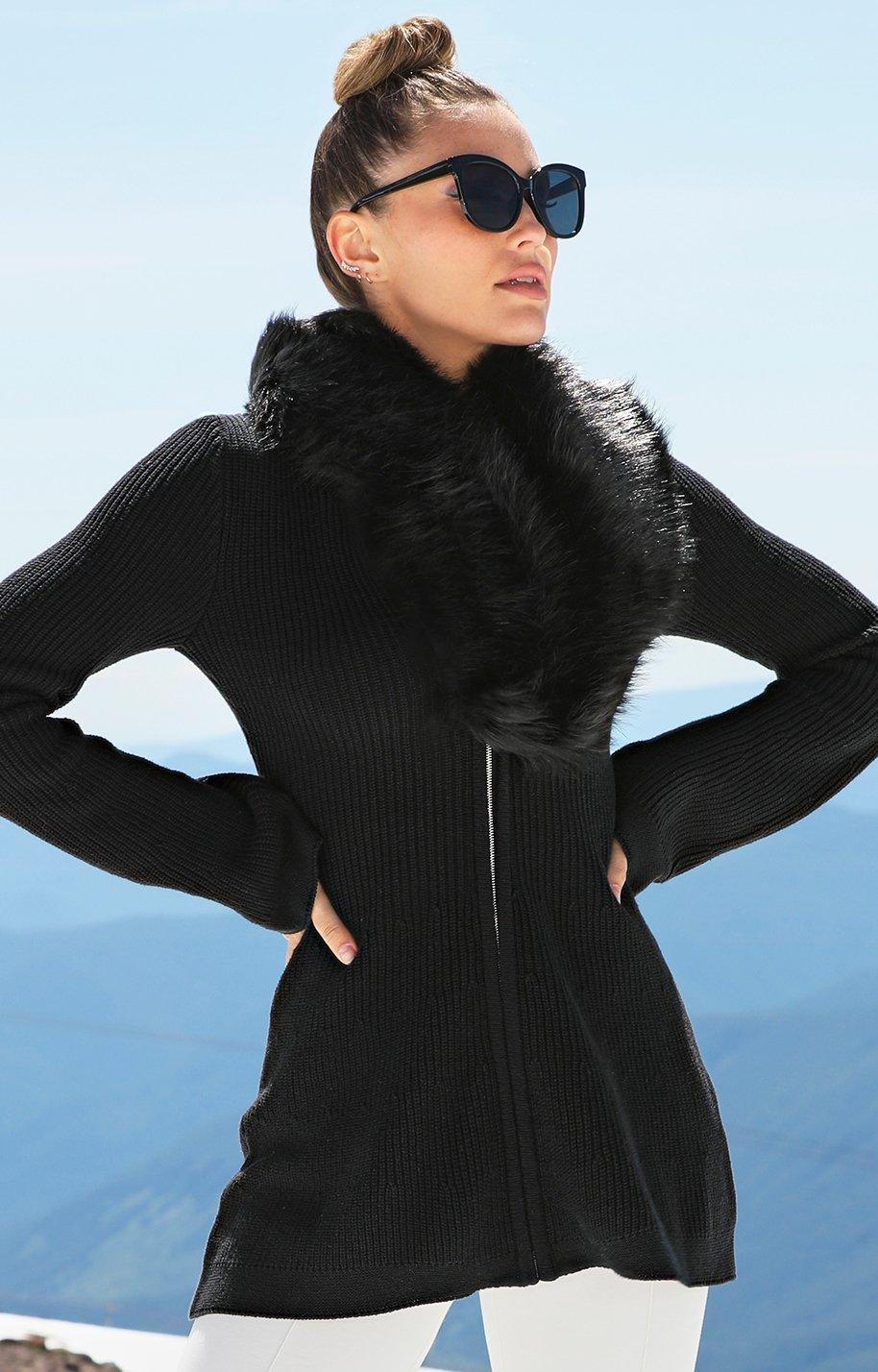 model wearing black jacket with faux fur, white pants, and sunglasses