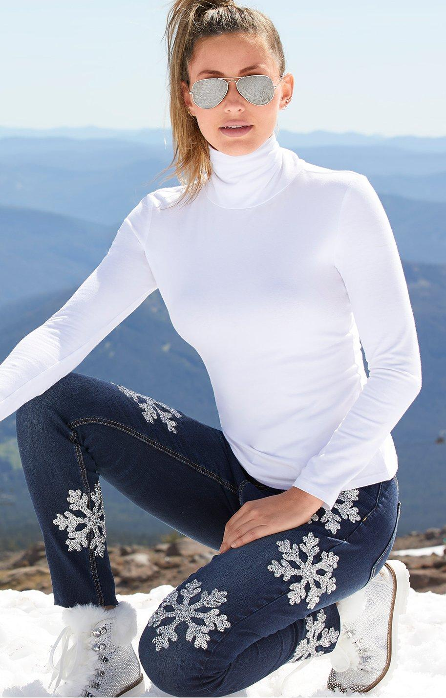 model wearing white long sleeve turtleneck, snowflake embellished jeans and faux fur silver boots