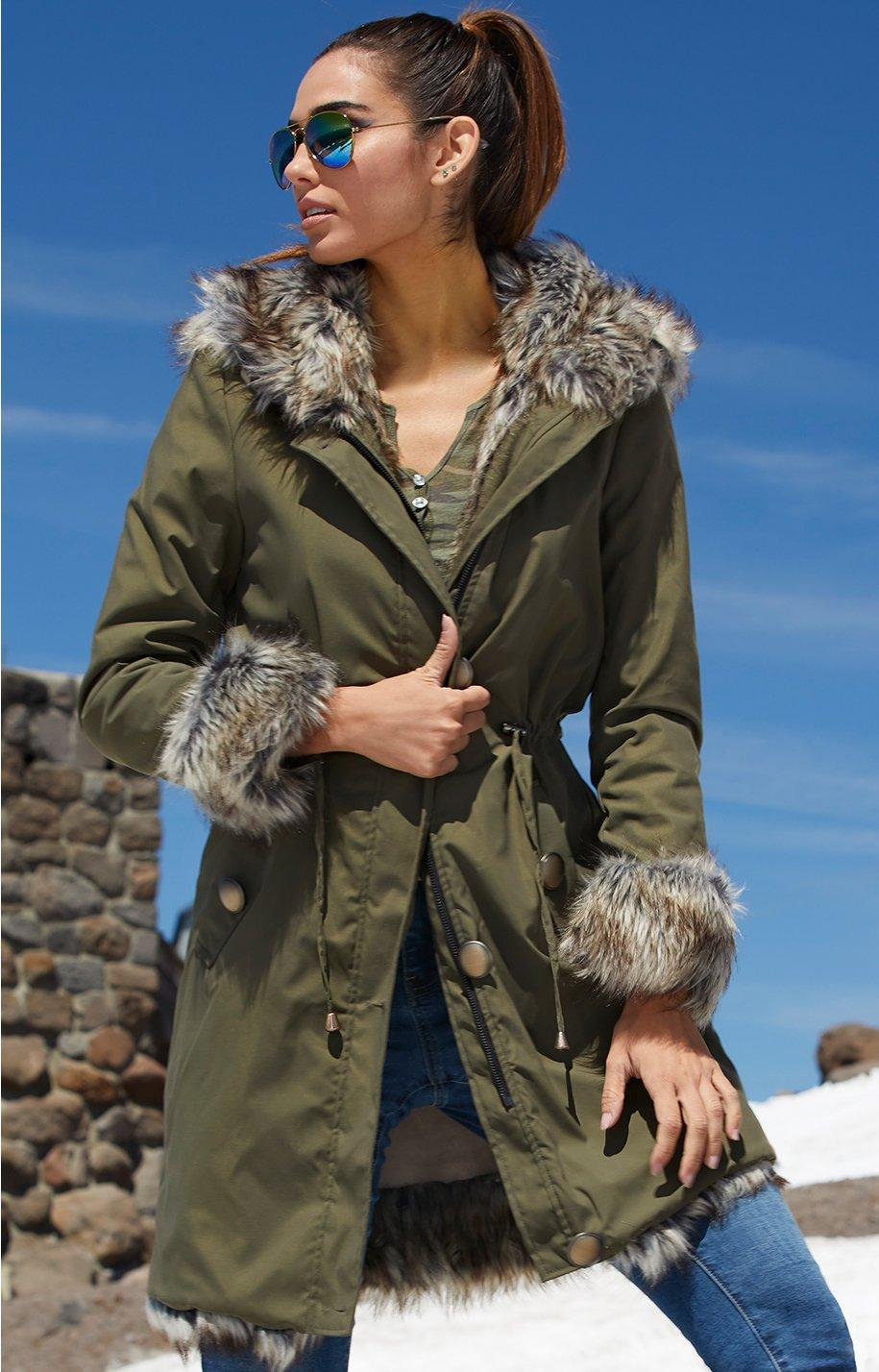 model wearing olive coat with faux fur lining over jeans