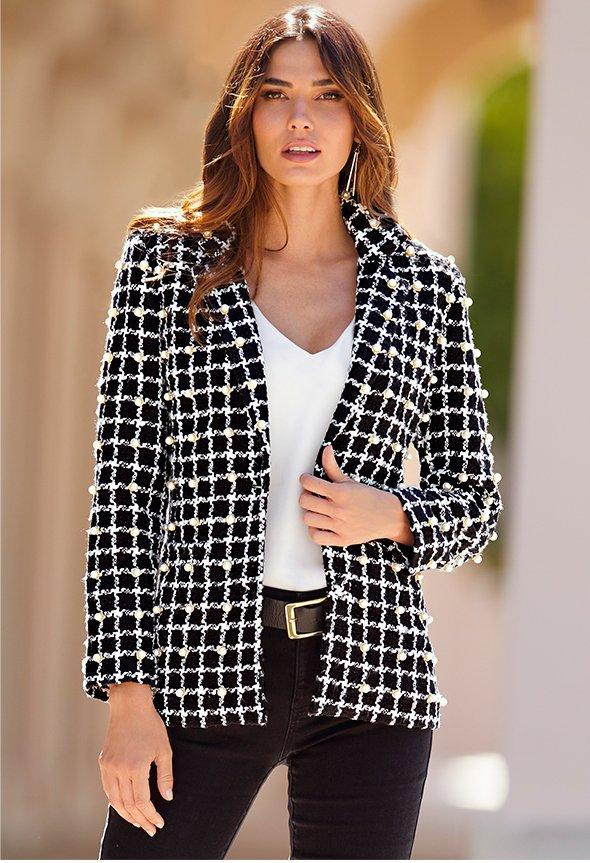 model wearing black and white plaid jacket over white top and black jeans