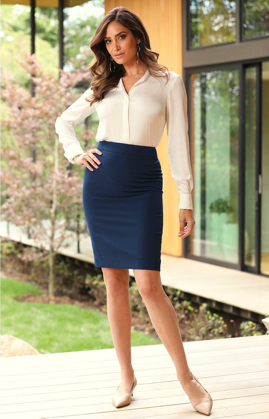 model wearing creme button up top tucked into navy pencil skirt