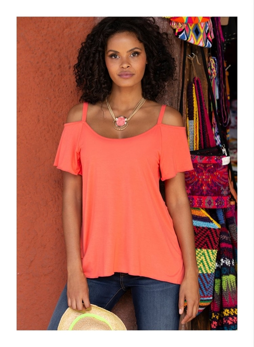 model wearing a short sleeve cold-shoulder coral top, jeans, and a pink necklace while holding a straw hat.