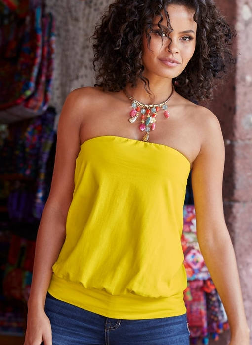 model wearing a blouson tube top in yellow, multicolored jewel necklace, and jeans.