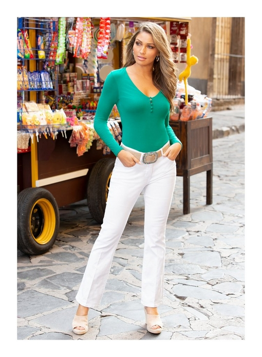 model wearing a long-sleeve covered button turquoise top, white jeans, white slip-on wedges, and a jewel embellished belt.