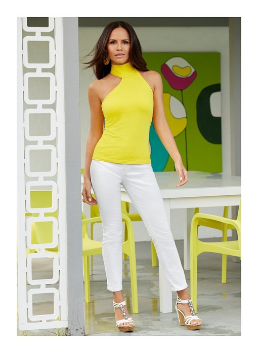 model wearing sleeveless yellow asymmetric mock neck top, white jeans, and wedges.