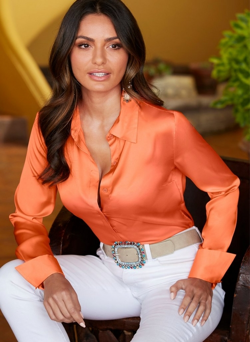 model wearing a coral button up charm blouse, white jeans, and a jeweled belt.
