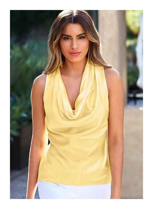 model wearing a pastel yellow cowl neck tank top and white jeans.