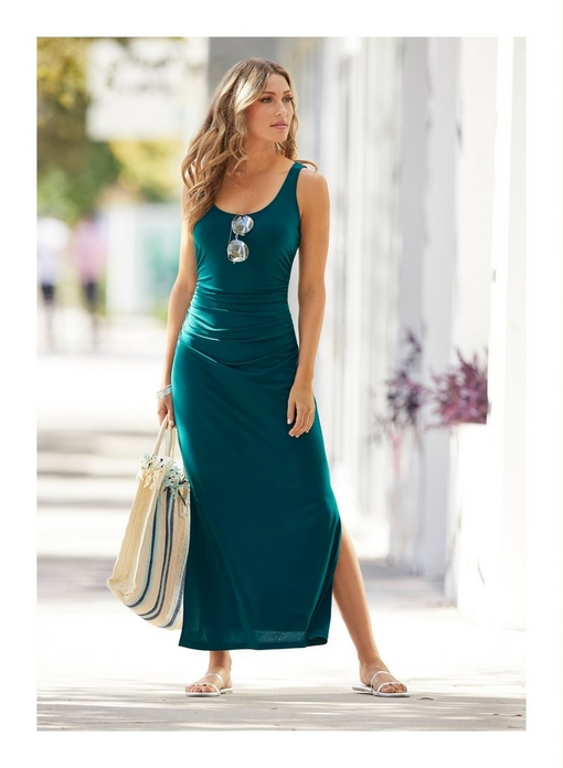 model wearing a teal sleeveless ruched maxi dress with sunglasses hanging on the neckline while holding a blue and white striped beach bag.
