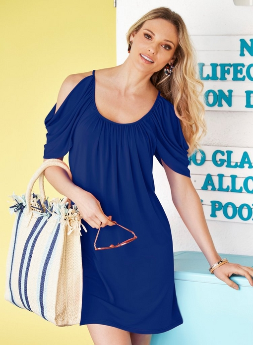 model wearing a blue cold-shoulder short sleeve dress while holding a blue and white striped beach bag and sunglasses.