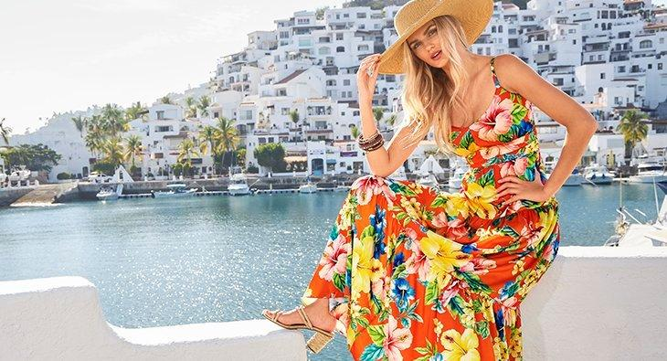 model wearing a multicolored floral printed sleeveless maxi dress and a straw hat.