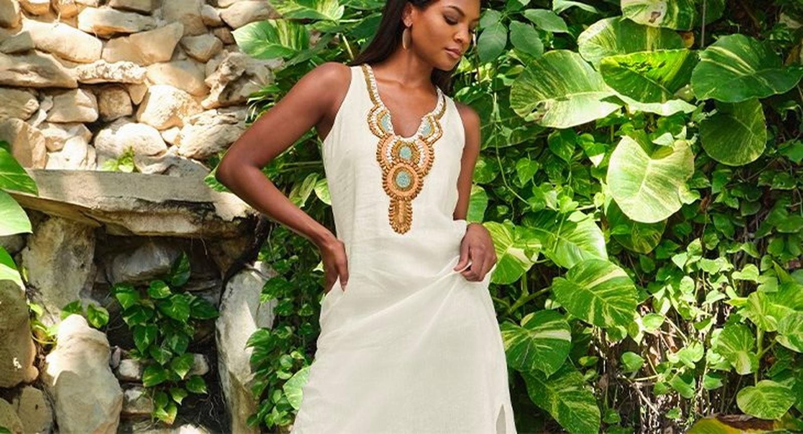 model wearing a white sleeveless linen maxi dress with an embellished neckline.