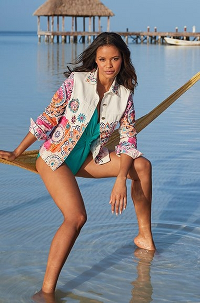 model wearing a white embellished denim jacket and a teal one-piece bathing suit with a strappy back.
