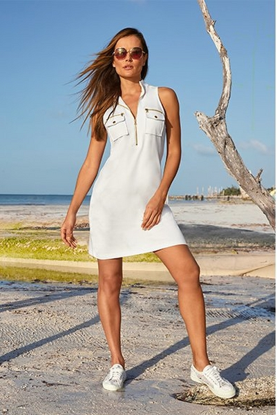 model wearing a white sleeveless sport dress, white sneakers, and sunglasses.