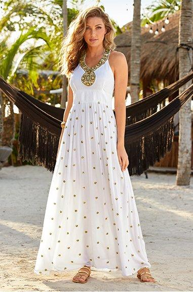 model wearing a white and gold polka dot maxi dress with a gold embellished neckline and gold strappy sandals.