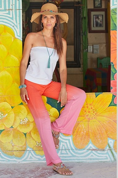 model wearing a white strapless blouson top, dip-dyed pink and orange pants, crystal embellished sandals, a teal tassel necklace, and a raffia hat.