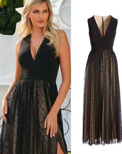 model wearing a black swiss dot overlay side slit gown.