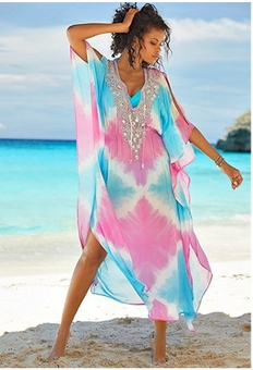 model wearing a pink and blue embellished caftan cover up while standing on the beach.