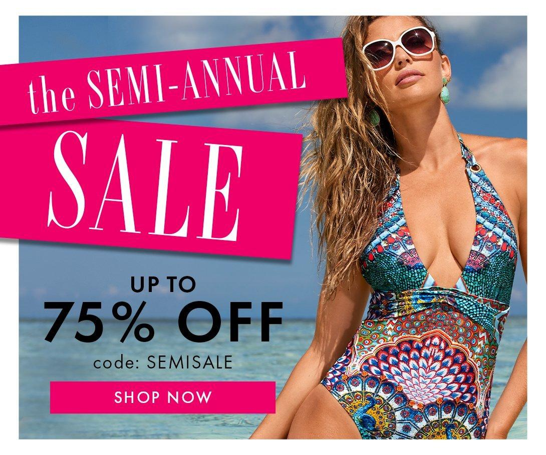 model wearing a multicolored deep v-neck one piece swimsuit and white sunglasses. text in pink, black, and white to the left.