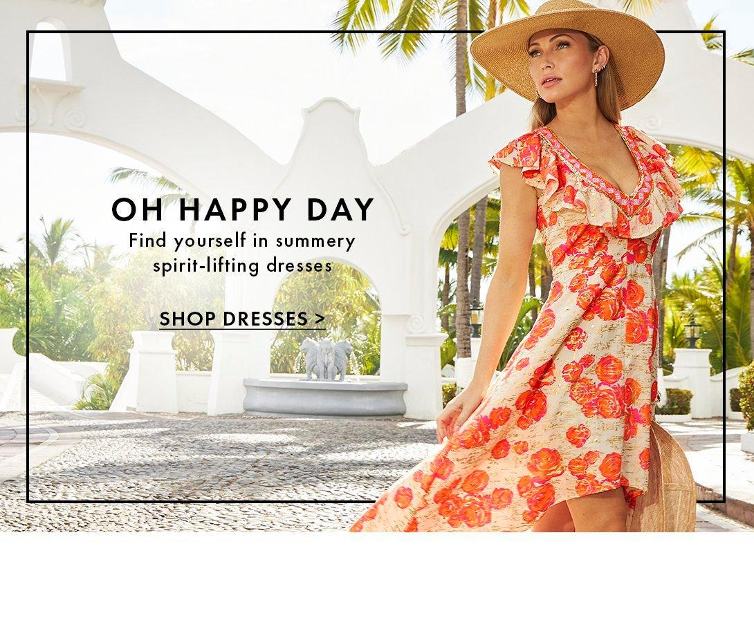 model wearing an orange and pink floral printed high-low maxi dress and straw hat.