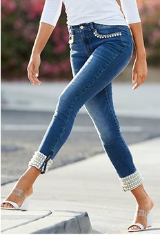 model wearing a white top, pearl embellished jeans, and white vinyl heels.