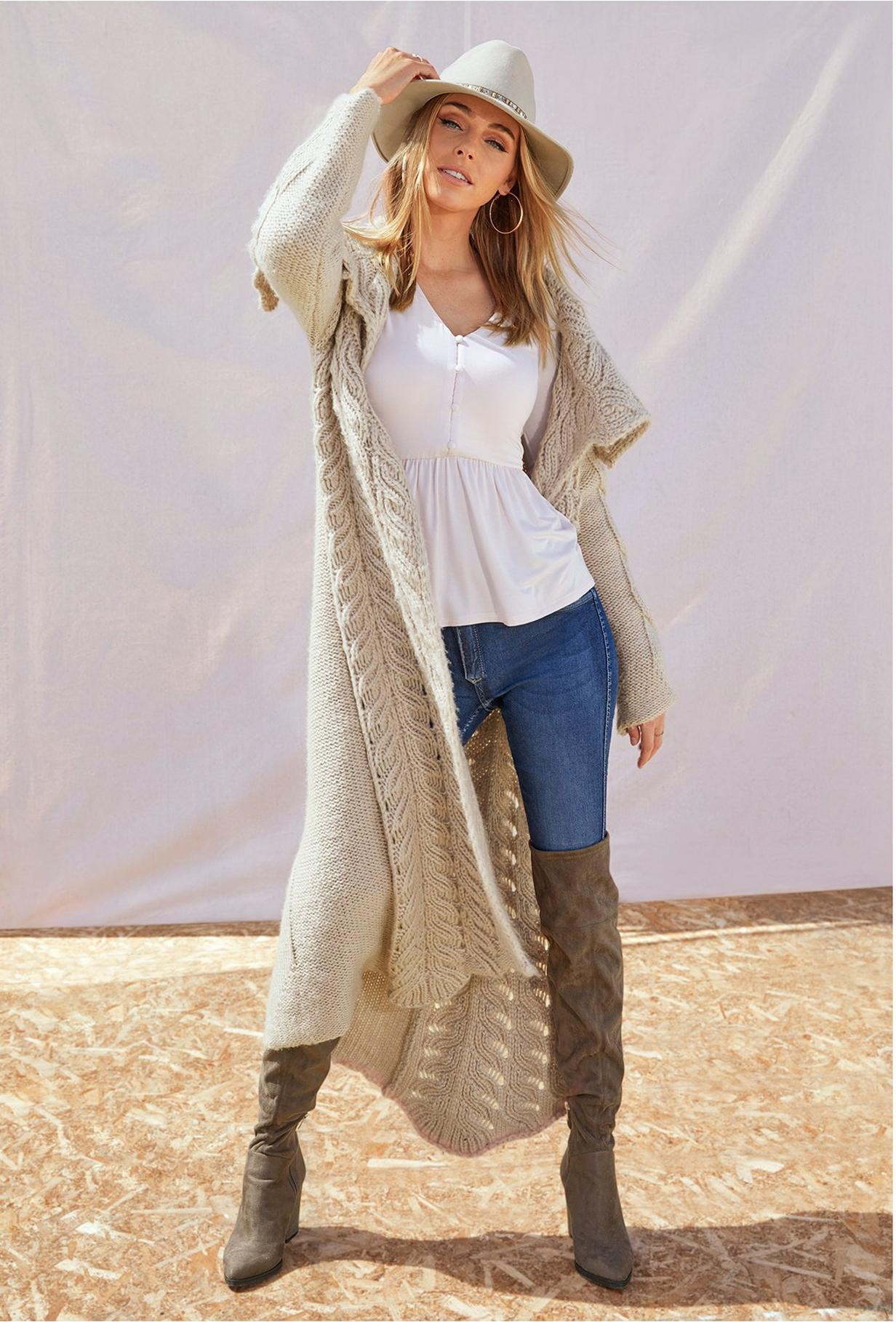 long cable sweater cardigan over poplin top, jeans, and boots