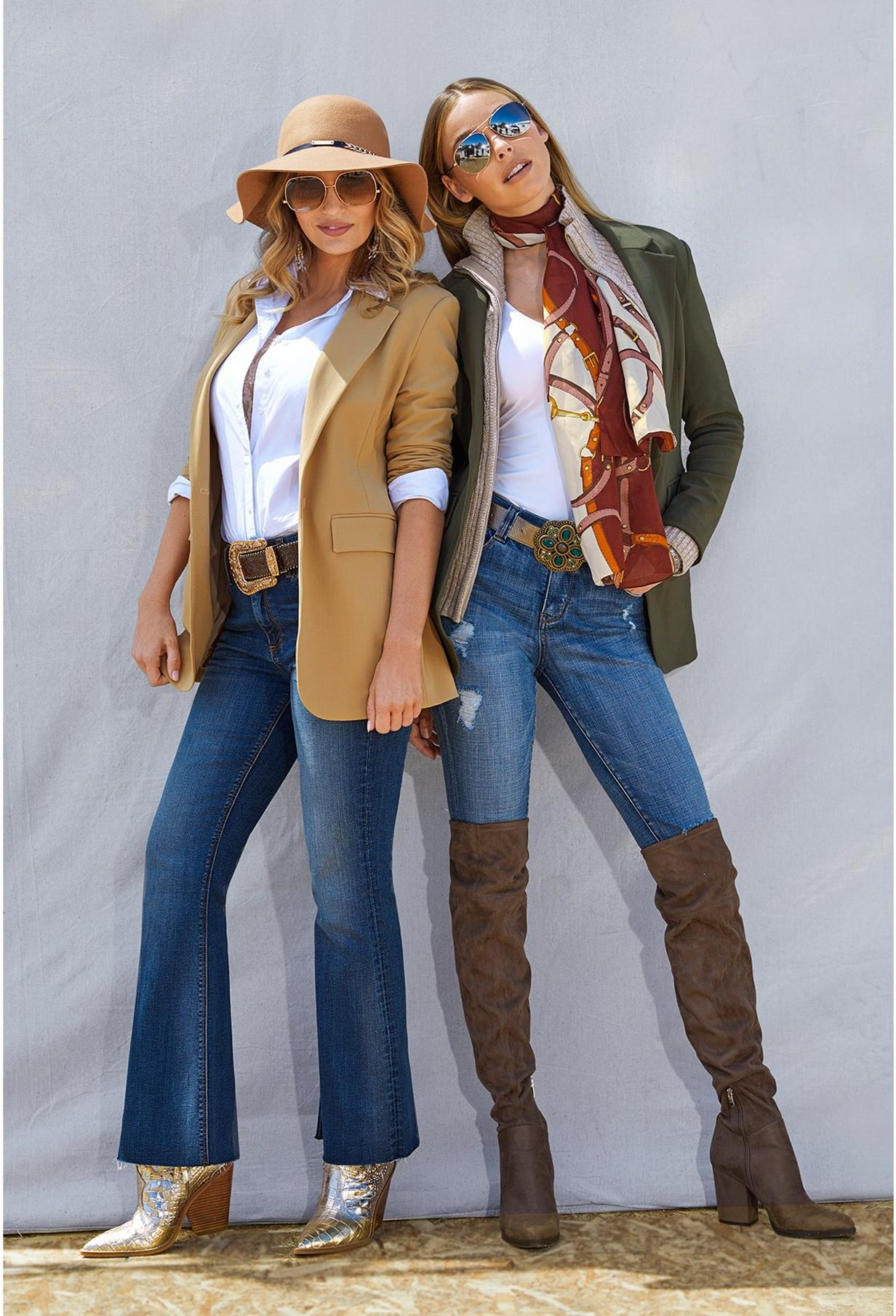 two women wearing blazers, poplin shirts, jeans, and boots