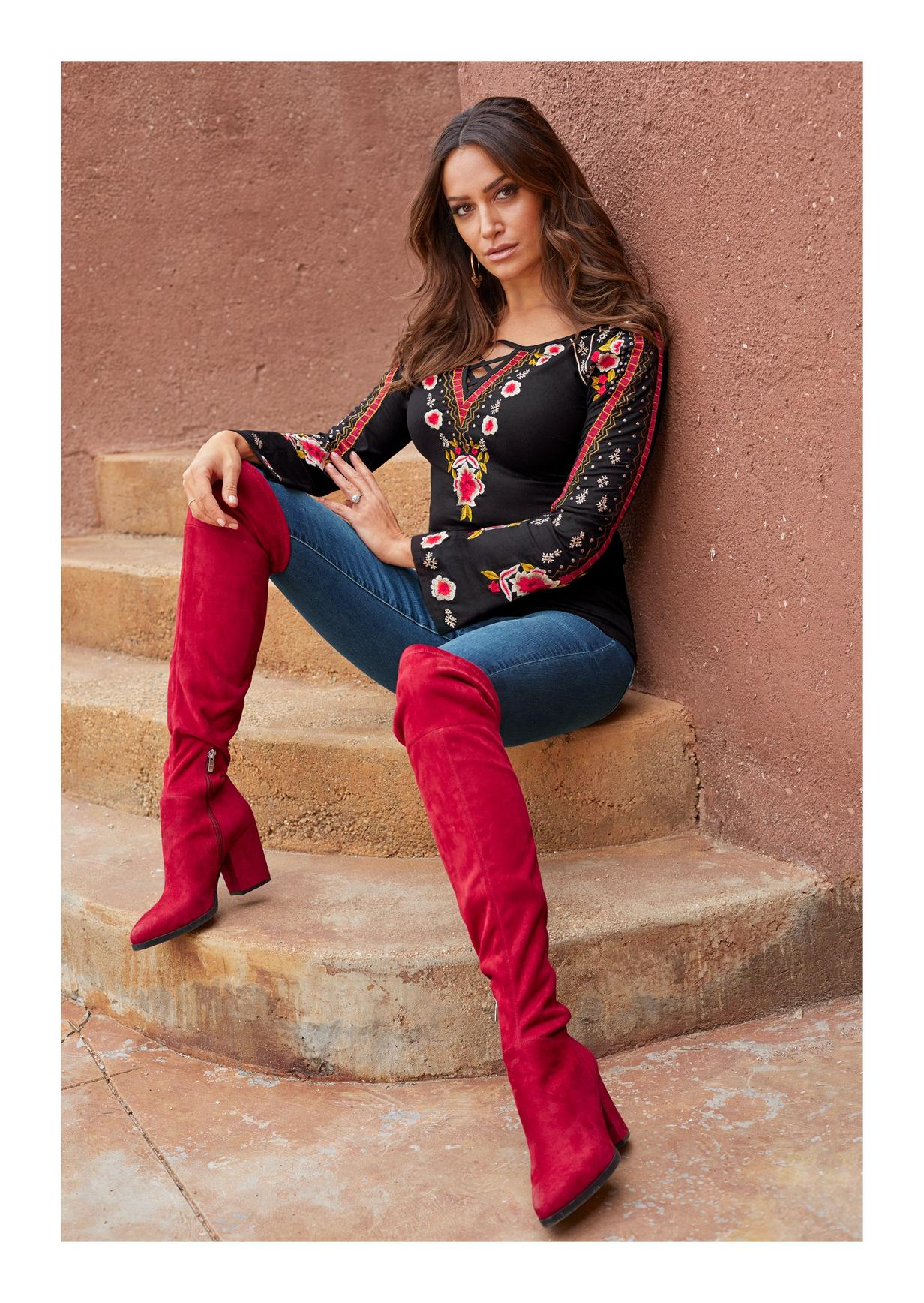 embroidered black top with jeans and red over-the-knee boots
