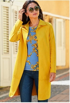 model wearing a yellow topper over a blue chain print top and jeans with sunglasses.