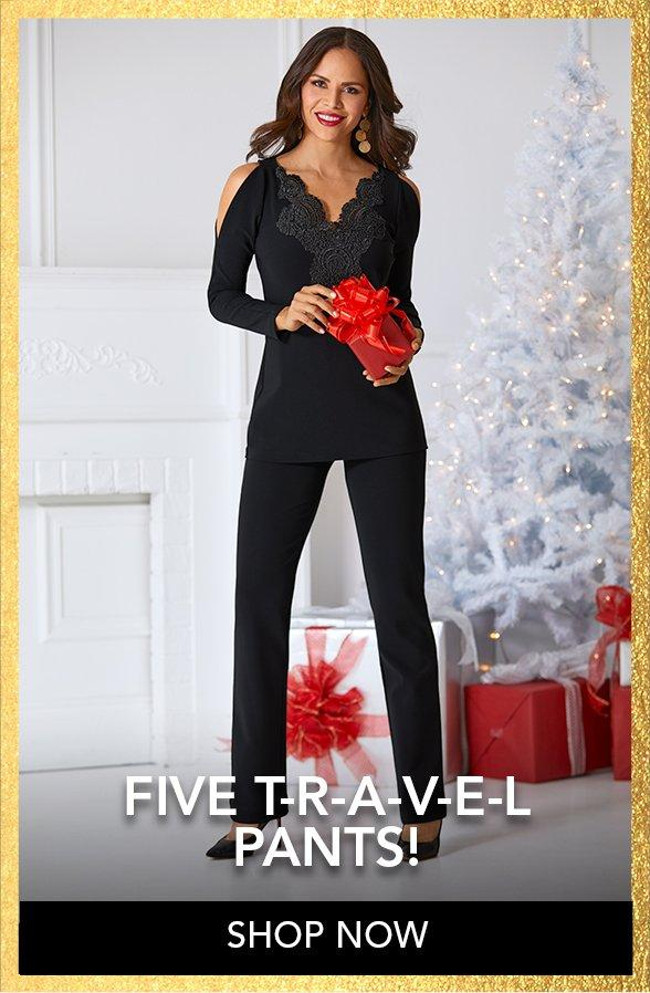 model wearing black lace cold shoulder top with black travel pants while holding a wrapped red gift.