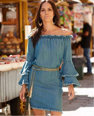 model wearing a denim tencel off-the-shoulder dress and a gold fringe belt.