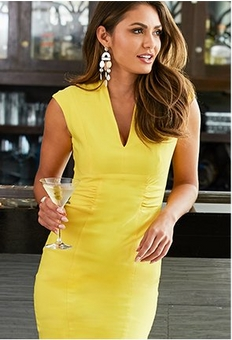 model wearing a yellow sheath dress with a v-neck and dangle earrings while holding a martini glass.