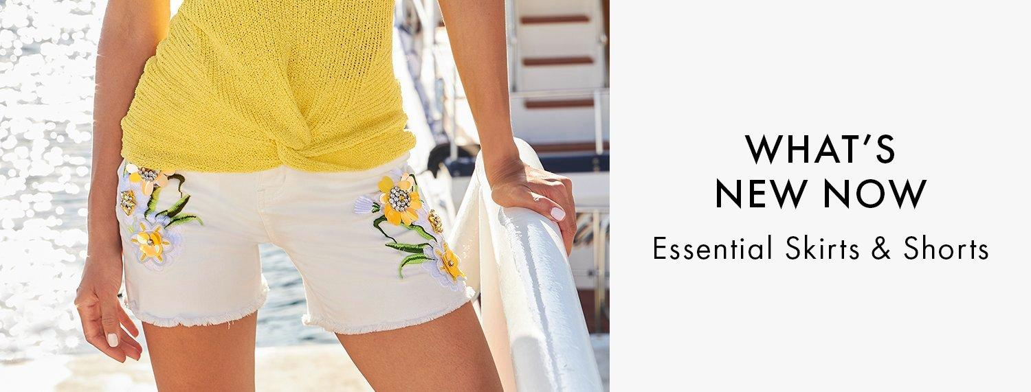 model wearing white denim shorts with flower embroidery and a yellow sleeveless tie front sweater.