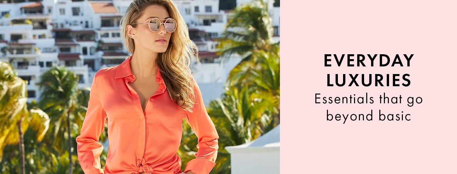 model wearing an orange button-down long sleeve charm top and sunglasses.
