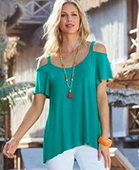 model wearing a teal cold-shoulder flutter sleeve top, white pants, and orange and green tassel necklace.